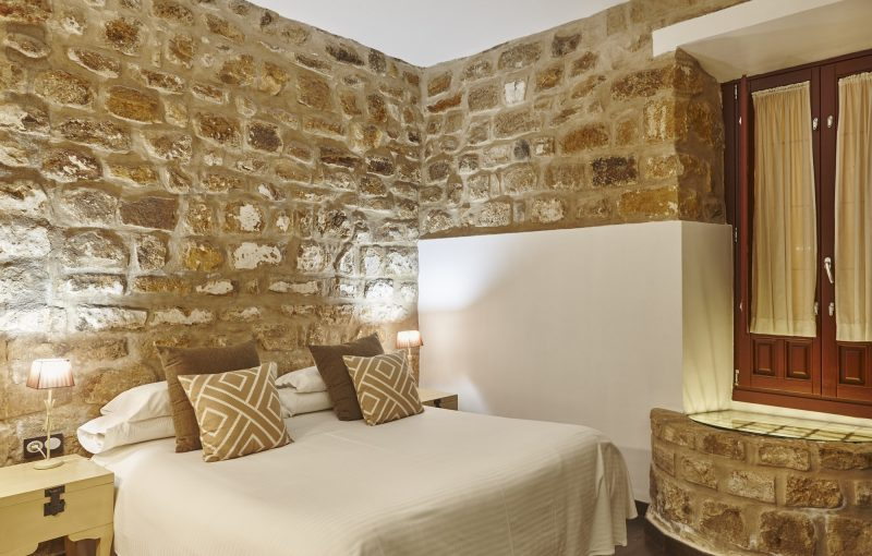 bedroom-with-stone-walls-comfortable-modern-hotel-room-interior-architecture.jpg